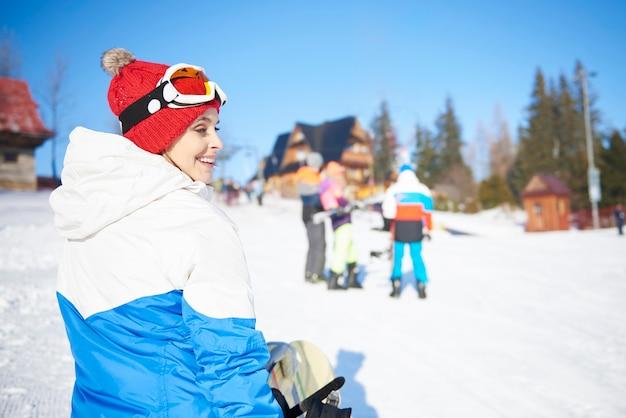 Chica de snowboard caminando por la ladera