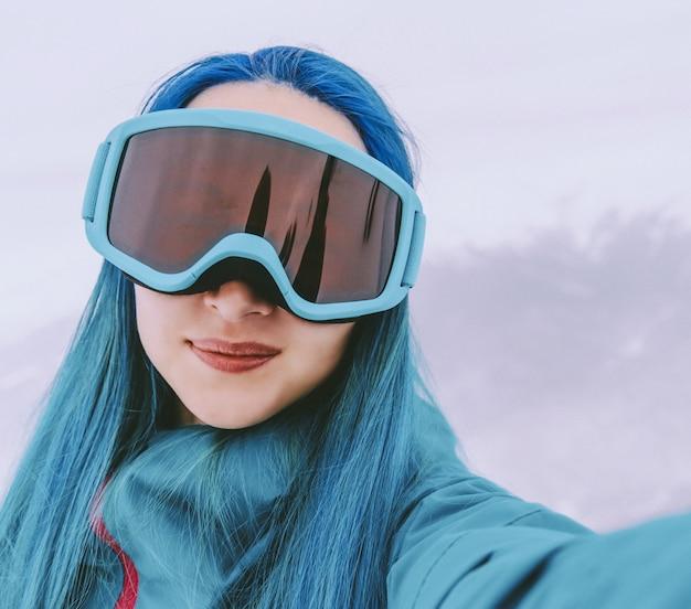 Chica de snowboarder haciendo selfie