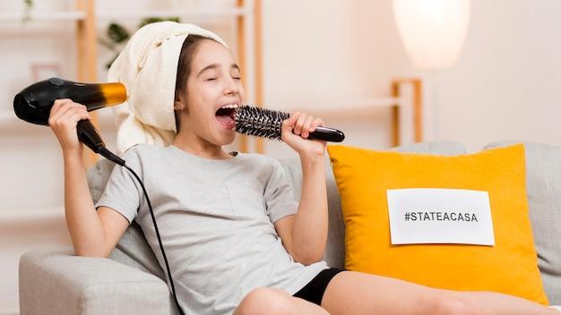 Chica en el sofá con secador de pelo y cepillo cantando
