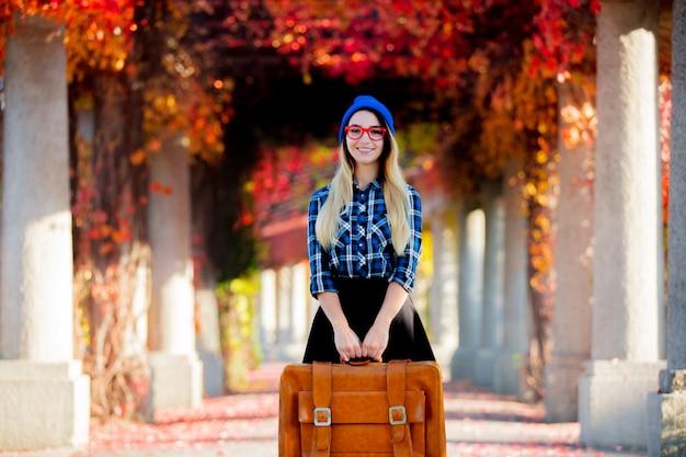 Chica con sombrero y camisa con maleta en callejón de uva roja