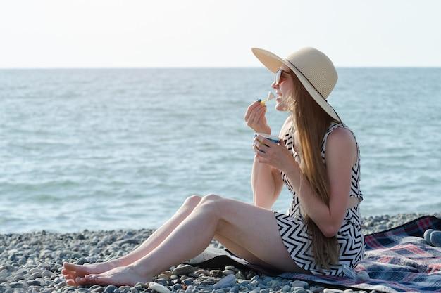 Chica con sombrero comiendo helado en la playa. día soleado