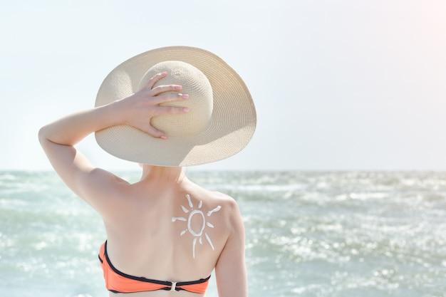 Chica con un sombrero contra el mar. en la parte posterior está pintado el sol.