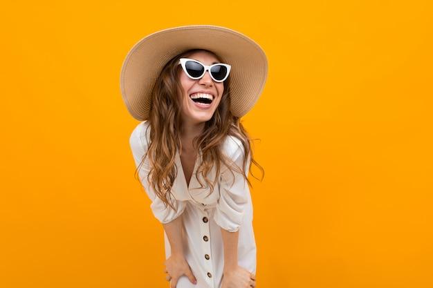 Chica con sombrero y gafas contra la pared amarilla se ríe con una amplia sonrisa