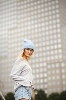 Chica con sombrero y gafas grita posando afuera