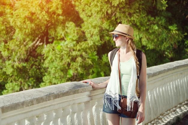 Chica con un sombrero y gafas de sol caminando en el parque. día soleado, parque