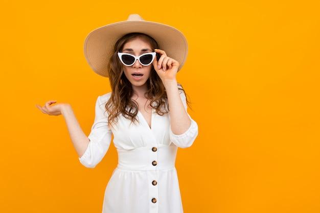 Chica con sombrero y gafas, un vestido blanco sobre un amarillo
