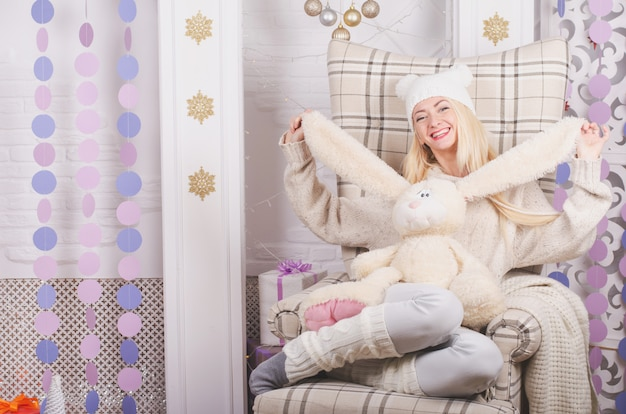 Chica con un sombrero gracioso abrazando a un conejito lindo en una acogedora silla de navidad, colores claros