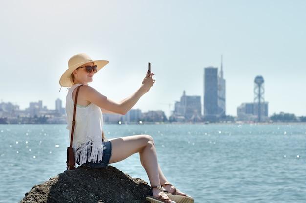 Chica con sombrero hace un selfie sentado en una roca junto al mar. ciudad a lo lejos. día soleado