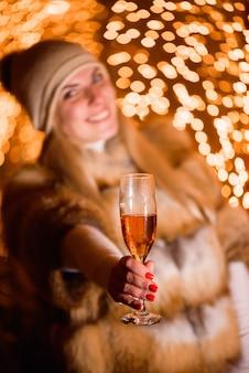 Chica con sombrero de invierno con copa de champán en la fiesta sobre fondo de oro brillante de vacaciones.
