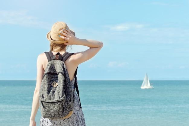 Chica con un sombrero con una mochila de pie en la costa. velero en la distancia. vista desde atrás