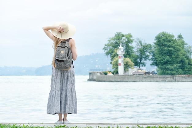 Chica con un sombrero con una mochila de pie en un muelle en el mar. montañas y faro en el fondo. vista trasera