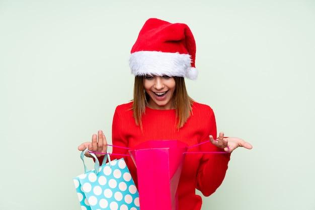 Chica con sombrero de navidad y con bolsa de compras sobre verde aislado