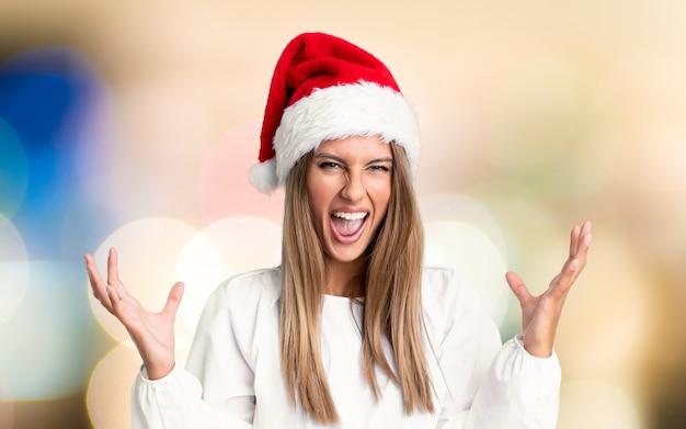 Chica con sombrero de navidad infeliz y frustrada con algo sobre una pared desenfocada