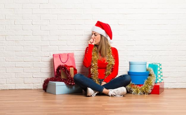 Chica con sombrero de navidad y muchos regalos celebrando las fiestas navideñas haciendo parar gest