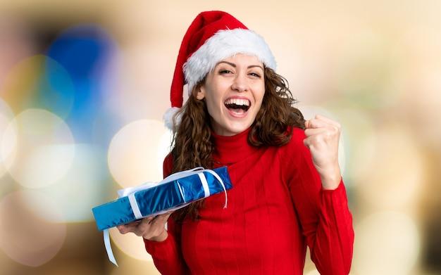 Chica con sombrero de navidad en pared desenfocada