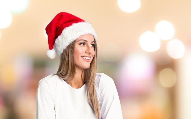 Chica con sombrero de navidad riendo sobre fondo desenfocado