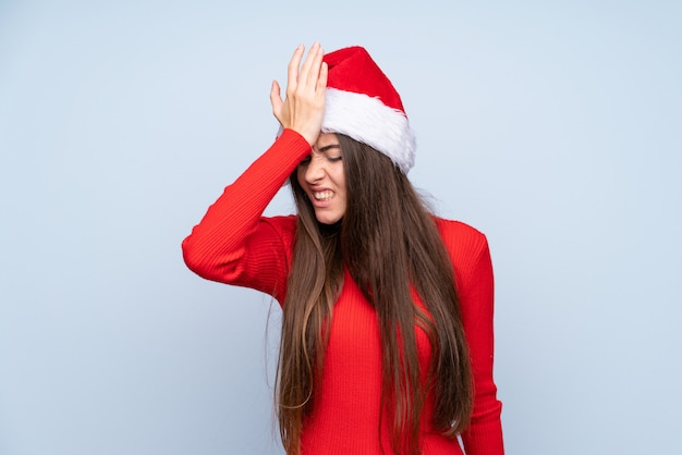 Chica con sombrero de navidad sobre azul aislado con dudas y con expresión de la cara confusa