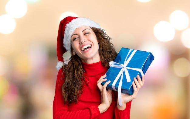 Chica con sombrero de navidad sobre fondo desenfocado