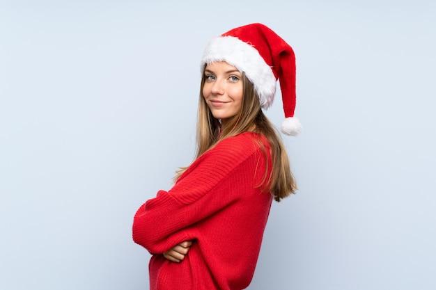 Chica con sombrero de navidad sobre pared azul aislado riendo