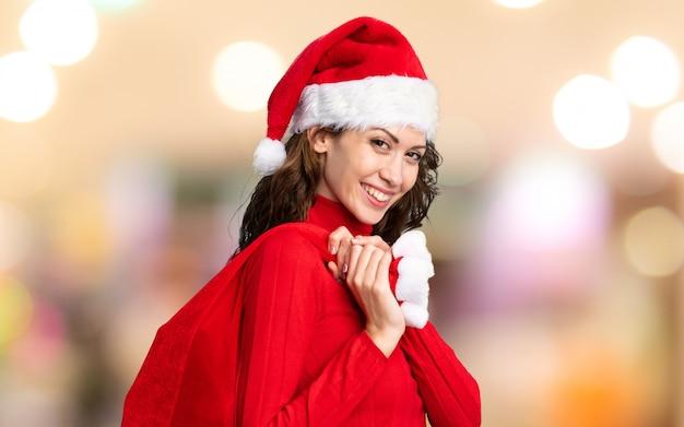 Chica con sombrero de navidad sosteniendo una bolsa de navidad llena de regalos en la pared desenfocada