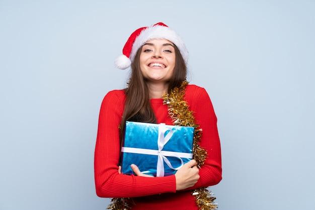 Chica con sombrero de navidad y sosteniendo un regalo sobre azul aislado