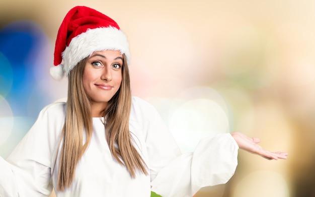 Chica con sombrero de navidad teniendo dudas y con expresión de la cara confusa sobre pared desenfocada
