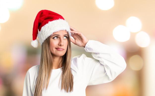 Chica con sombrero de navidad teniendo dudas y con expresión de la cara confusa