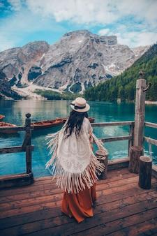 Chica con sombrero de paja en el lago turquesa con barcos de madera en las montañas.