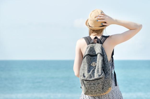 Chica en un sombrero de pie en la costa