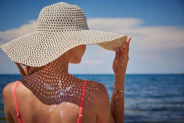 Chica con sombrero y protector solar en forma de sol en la espalda.