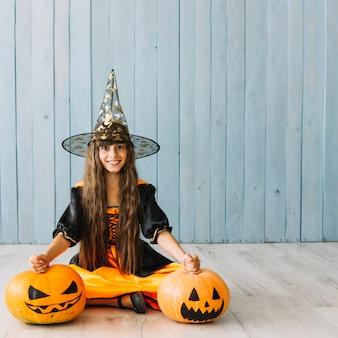 Chica en sombrero puntiagudo sentado en el piso con calabazas