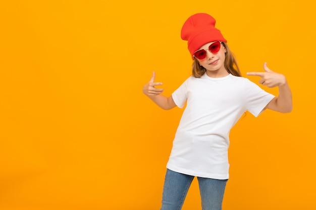 Chica con un sombrero rojo y gafas en una camiseta con maqueta en una pared amarilla