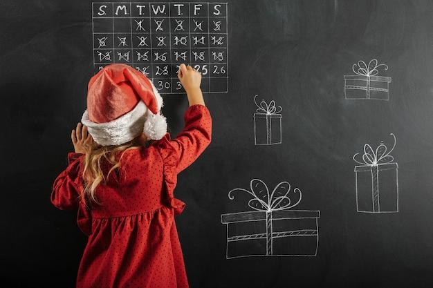 Chica con sombrero de santa claus dibuja dibujos de navidad en la pizarra