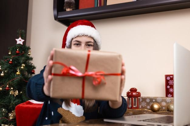 Chica con sombrero de santa claus habla y da un regalo usando una computadora portátil para videollamadas a amigos y padres. la habitación está decorada de forma festiva. navidad durante el coronavirus.