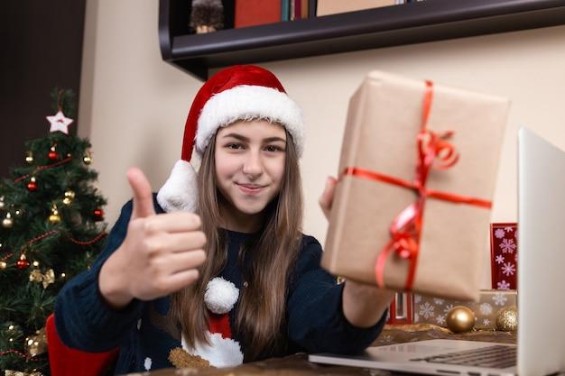 Chica con sombrero de santa claus habla y da un regalo usando una computadora portátil para videollamadas a amigos y padres. la habitación está decorada de forma festiva.