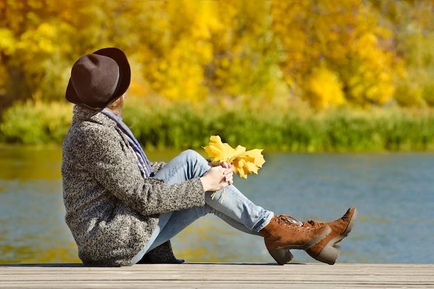 Chica del sombrero sentada en el muelle. día de otoño. vista lateral