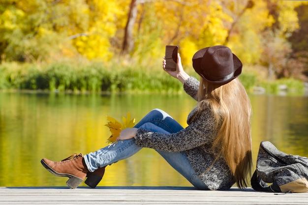 Chica del sombrero sentada en el muelle y hace selfie. día soleado de otoño. vista lateral