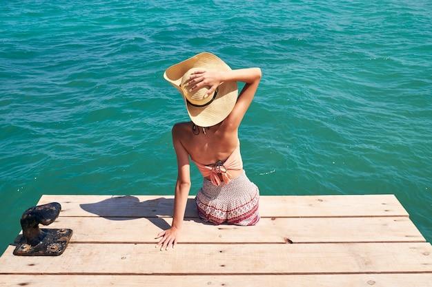 Chica con sombrero sentado en un muelle de madera