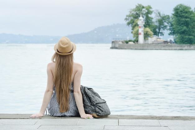 Chica del sombrero sentado en el muelle. mar y pequeño faro en la distancia. vista trasera