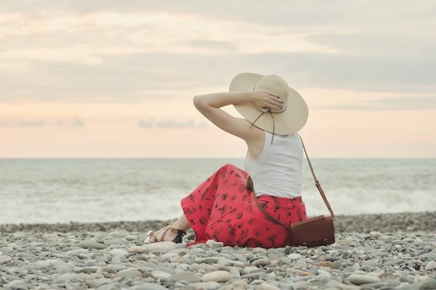 Chica con un sombrero se sienta en una playa de guijarros.