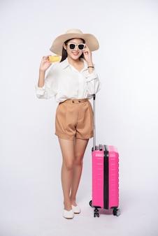Chica con sombrero con tarjeta de crédito y maleta para viajar