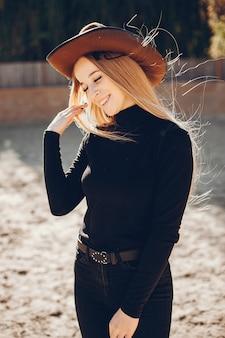 Chica en un sombrero de vaqueros en un rancho