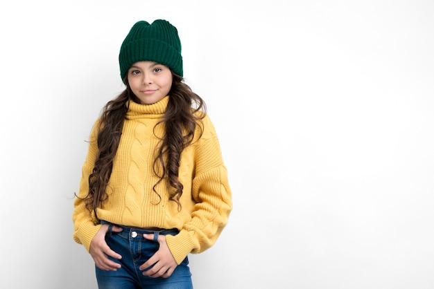 Chica con sombrero verde y suéter amarillo