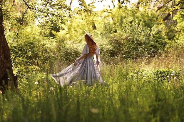 Chica con sombrero y vestido en el jardín bajo el sol de verano en un paseo
