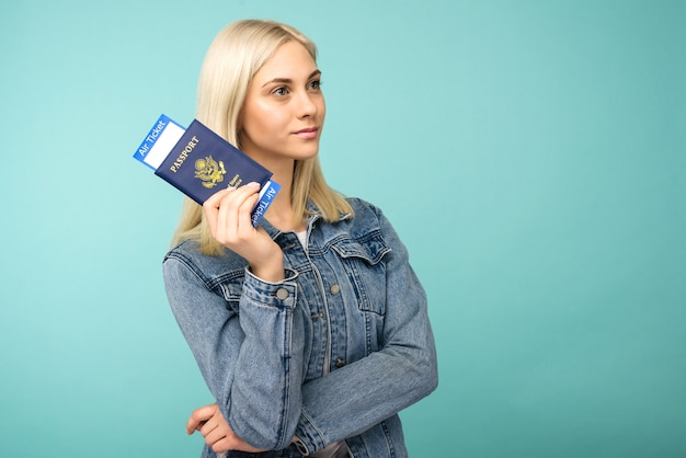 Chica soñadora en una chaqueta de mezclilla tiene un pasaporte con billetes de avión