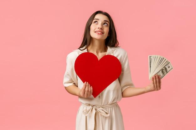 Chica soñadora joven y linda imaginando cosas, con ganas de encontrar el amor verdadero no le importa el dinero atractiva mujer atractiva mirando pensativo y sonriente, con tarjeta de corazón y dólares en efectivo, pared rosa