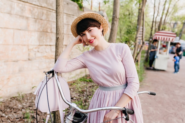 Chica soñadora en traje elegante posando durante el viaje en bicicleta de pie cerca del muro de piedra en la calle