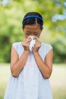 Chica sonarse la nariz con pañuelo mientras estornuda