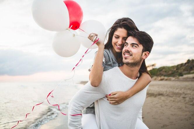 Chica sonriendo con globos mientras su novio la lleva en su espalda