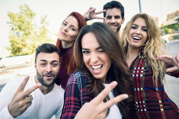 Chica sonriendo haciendo una autofoto con sus amigos alrededor